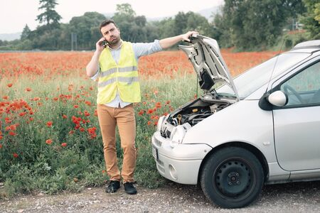 Man calling for help with mobile phone. Broken down car on the road. Traveling problem.