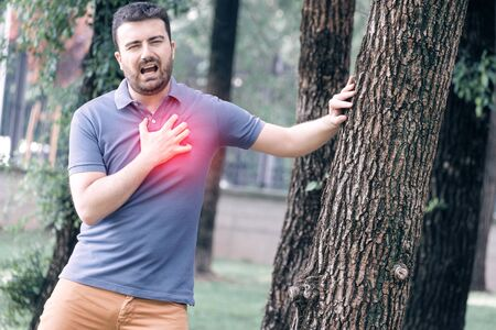 Man clutching his chest from sudden pain.Heart attack symptom concept.
