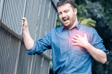 Severe heartache.Man pressing on chest with painful expression fist aid needed. Stok Fotoğraf