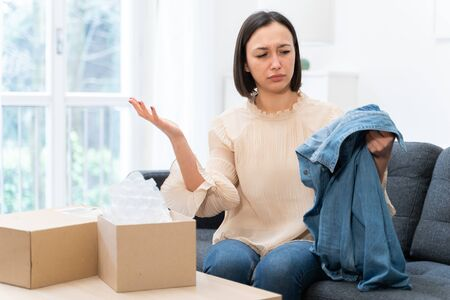 Dissatisfied young woman taking clothes out of box and mistake delivery