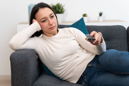 Young girl portrait watching television using remote Banque d'images