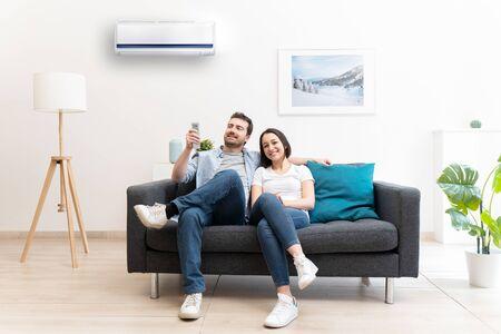 Happy couple freshen up using air conditioner at home Archivio Fotografico