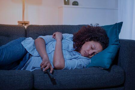 African woman feeling lazy and sleepy on the sofa