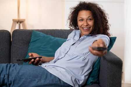 Portrait of black woman watching tv at home