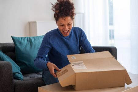 Black woman portrait unboxing package after delivery