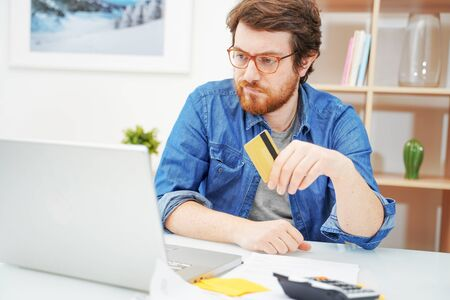 Worried man sitting in home office and using credit card Standard-Bild