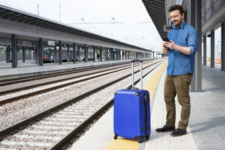 Man with mobile phone and carry on roller in train station platform