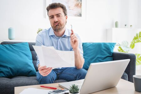 Troubled guy calculating bills tax expenses and counting home business