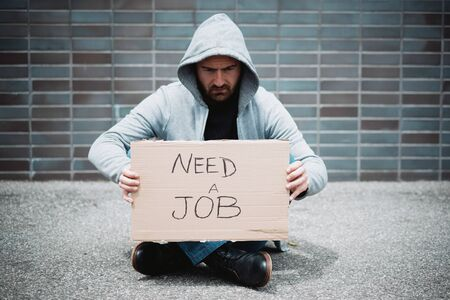 Jobless worker after job loss begging in the city street