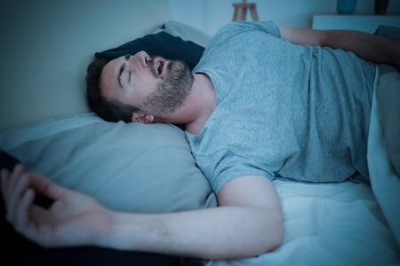 Man snorer in bed breathing with open mouth