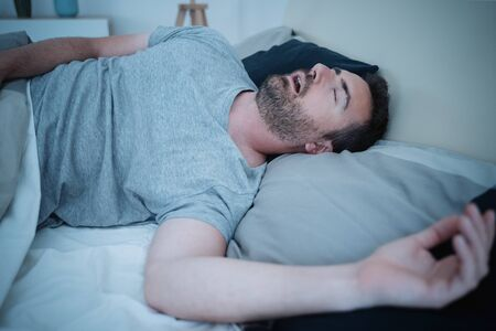 Man snoring loudly in his bed during night time