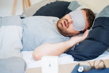 One guy sleeping and wearing an eye mask
