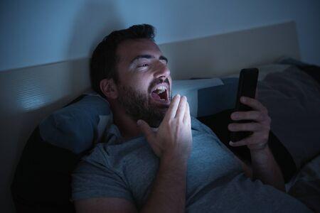 Man in bed watching smartphone display