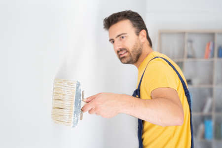 Professional painter portrait whitewashing the wall, focus on the brush