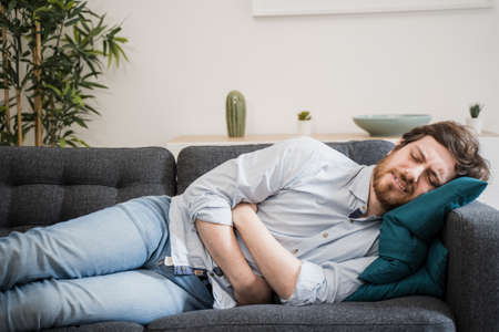 Guy feeling unwell with a stomach ache while sitting at home