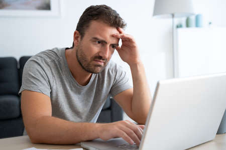 Worried man checking bad news on his computer