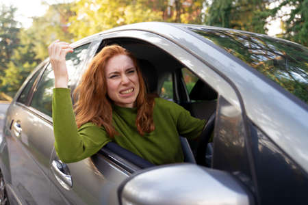 Frustrated woman driving her car and gesturing roughly Foto de archivo