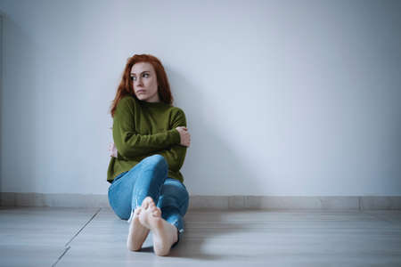 Depressed young girl on the parquet floor
