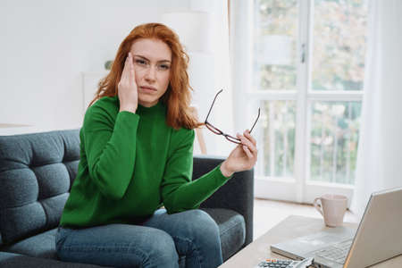 One young redhead woman suffers for head pain