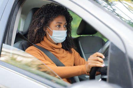 Young woman wearing face mask and driving car