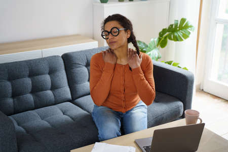 Black woman is suffering neck pain working from home