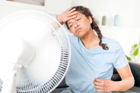 Black woman refreshing from summer heat at home