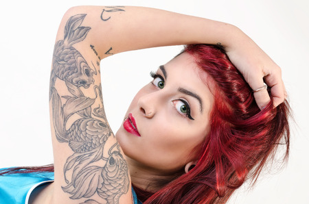 beautiful redhead girl with tattoos in pinup style and white background photo