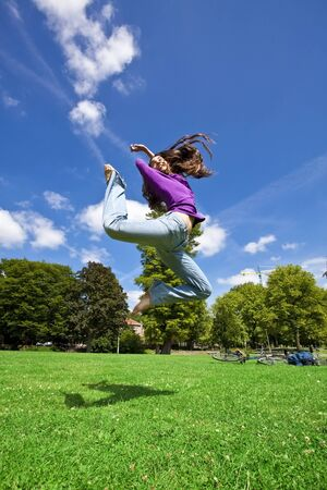young girl dancing happy in a park