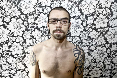 skinny tattoo guy on floral background Stock Photo