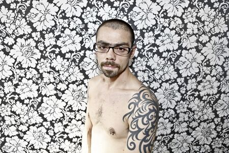 bad skin: skinny tattoo guy on floral background Stock Photo