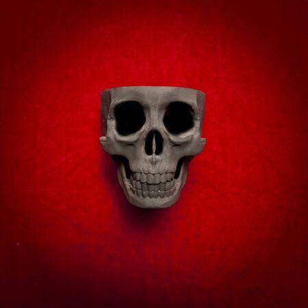 velvet background: black scary human skull on red velvet background