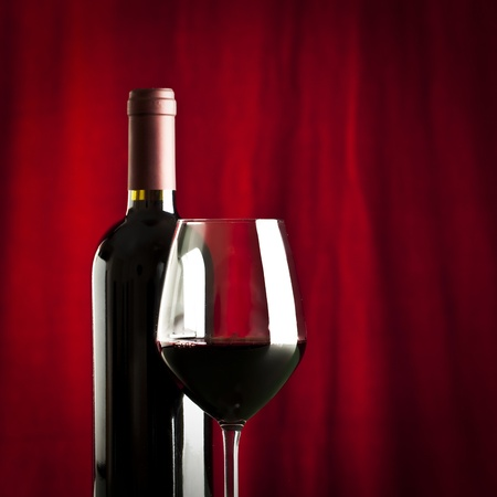 a glass of red wine and a bottle on red background photo