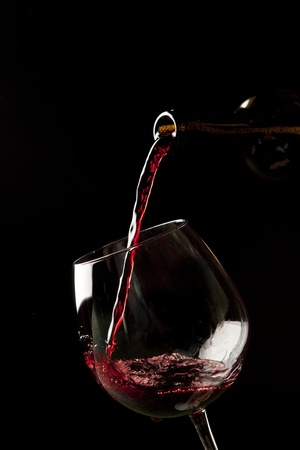 Red wine splash on a glass on black background. Stock Photo