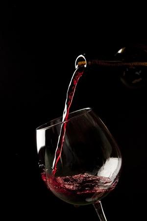 black liquid: Red wine splash on a glass on black background. Stock Photo