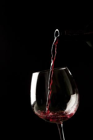 Red wine splash on a glass on black background. photo