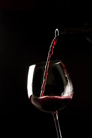 Red wine splash on a glass on black background. Stock Photo - 9733815