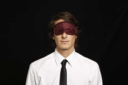 young businessman with eyes covered by sleep mask Stock Photo