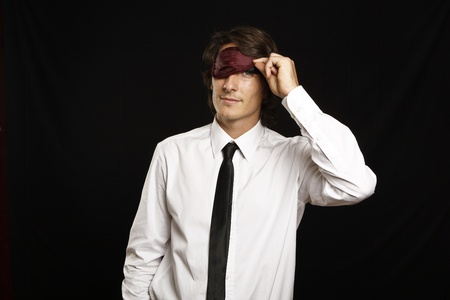 young businessman looking below sleep mask photo