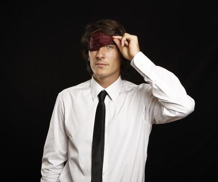 sleep mask: young businessman looking below sleep mask