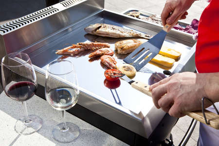 professional chef cooking fish on a barbeque photo