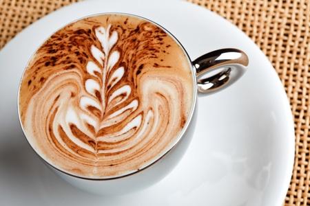 barista: art latte on a cappuccino coffe cup