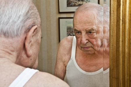 elder pensive at the mirror Stock Photo