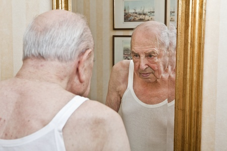 elder pensive at the mirror Stock Photo