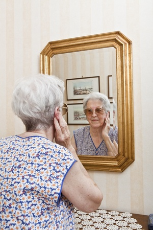 elder lady pensive at the mirror photo
