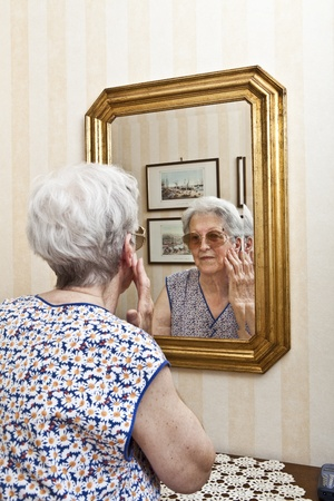 antique mirror: elder lady pensive at the mirror