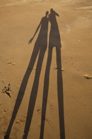 Long shadow of young couple on beach sand photo