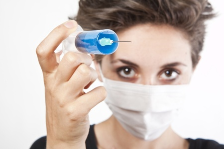 needle syringe infection: Young pretty nurse in mask with syringe