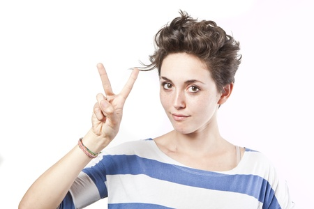 beautiful young girl making a victory sign isolated over white background photo