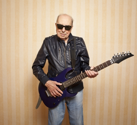 cool fashion elder man with electric guitar Stock Photo
