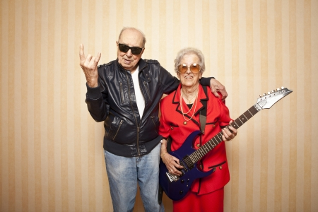 active senior: cool fashion elder couple with electric guitar Stock Photo